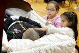Ariana Munoz, cq, 11, left, and another girl visit the body of Marine Cpl. Brett Lundstrom, who...