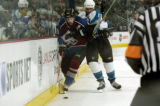 (DENVER, Colo., May 4, 2004) San Jose Sharks Patrick McCauley hits Colorado Avalance player Peter...