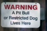 Sign posted on the front of the  home where  Moses , a 7 year-old American Staffordshire lives...