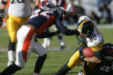935 Steelers #80 Cedrick Wilson is brought down by Broncos #25 Nnick Ferguson, right, and #22...