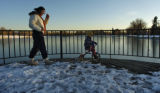Cynthia Lemann (cq) walks with Sebastian Chambers, 3 years old, on the dock at Grasmere Lake in...