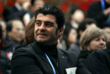 Italian skiing legend Alberto Tomba listens to a speaker before the grand opening of the Olympic...
