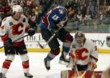 Colorado Avalanche player Dan Hinote, middle, leaps out of the way of a shot on goal as Calgary...