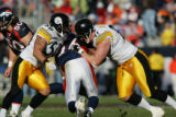 1315 Broncos Tatum Bell is sandwiched by Steelers #50 Larry Foote and #91 Aaron Smith during the...