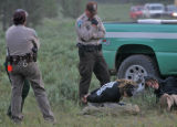 U.S. Forest Service law enforcement keep a close eye on Rainbow Family members who were caught in...
