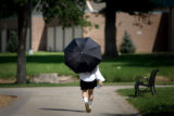 Dina Espinoza, cq, Denver, takes a stroll through Washington Park using an umbrella for shade on...