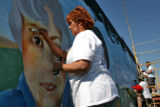 Student Iris Scadden (cq), paints on a mural on the side of Ace Jewelry at 7280 Monaco St. on...