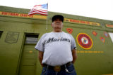 Prominent Denver artist and former Marine Ray Espinoza, cq, stand in front of a mural at E 47th...