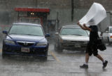 A unidentified pedestrian braves the heavy afternoon rain with a garbage bag over his head as he...