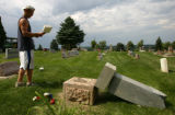 Dan Wall, CQ, 21, a maintenance worker at the Arvada Cemetery assesses the damage done by vandals...