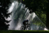 MJM316  As the sun streaks behind a sprinkler, a bicyclist gets in a early morning ride Wednesday...