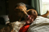 Tami Bishop, 36, of Denver gets her face licked as she sits with her two dogs Zander and Hidye in...