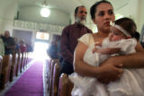 Marie Martinez, cq, holds her daughter, Celina Romero, before her baptism at Our Lady of Guadalupe...