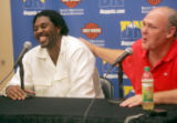 Newly re-signed F/C Nene, left, gets a pat on the back from Denver Nuggets head coach George Karl,...
