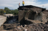 CDOT workers evaluate a  large section of Hwy. 115 Thursday morning, July 6,2006 , which was...