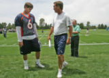 Denver Broncos head coach Mike Shanahan, right, tells rookie quarterback Jay Cutler, left, to go...