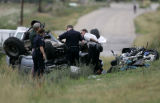 Investigators survey the wreckage of a silver Toyota pickup truck involved in a fatal accident...