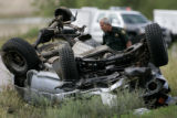 An officer with the Jefferson County Sheriffs Department  surveys the wreckage of a silver Toyota...