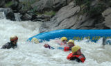 Raft guide Nick Goymerick prepares to gather his rafting guests after flipping in the class IV...