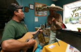 Roberto Garcia plays a tune to the delight of  Lorenzo Chavez at the Verderaime Bakery in Aguilar,...