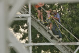 Rescue crews at Lakeside Amusement park help two passengers down the track of the Cyclone roller...
