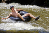 C.J. Fox (cq), 21, of Lakewood prepares to drop over a small waterfall on Boulder Creek Monday...