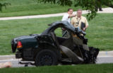 Police investigators look over the scene at a fatal one vehicle car crash near the corner of...