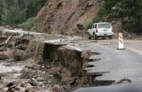 A Douglas County vehicle  makes its way around one of dozens washed out sections of road along HWY...