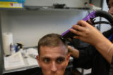 Michael Guerrin, 21, of Florida, gets his military haircut, Wednesday July 12, 2006 as he arrives...