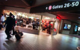 Two pilots walk past the Bon Voyage retail store at the entrance to the B Concourse at Pittsburgh...