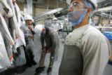 Employees put on safety equipment as they return from a break at the Swift and Company Greeley...