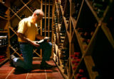 Smith Fork Ranch owner Marley Hodgson (cq) looks through some of the 300 different labels of wine...