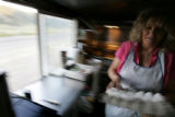 "Dawn Schumann-Keithley (cq) makes breakfast burritos in her ""Pink Pig"" mobile catering..."