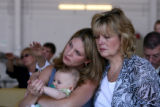Kim Egan, cq, holds her son Benjamin Egan, 6 months-old, as Gretchen Roske, cq, hugs Kim during a...