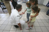 Doug (cq) Devlin, takes the glad hand of Emily Hart,8, balanced on her sisters, Elizabeth,9, and...