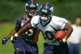 Rookie running back Mike Bell (#20) takes off with a pass while being chased by corner back Roc...
