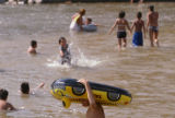 KAS076 An unidentified boy wades back up the Platte River with a raft at Confluence Park on...
