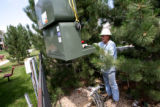 Xcel Energy foreman John Bass, cq, carefully guides a new transformer Monday July 17, 2006 as it...