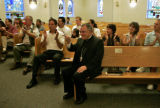 Archbishop Charles J. Chaput, middle, sits in the pews as he acknowledges other members of the...