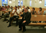 Archbishop Charles J. Chaput, middle, sits in the acknowledges other members of the clergy for...