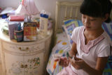 KAS039 Anna Zhong, 10, shows Chinese money to a reporter in her room at her home in Centennial on...