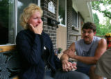 Julie Carlson, left, cries while her husband Steve Carlson, holds her hand at their home in...