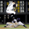 Rockies shortstop Clint Barmes  goes high over Tony Gwynn Jr. to complete a double play to end the...