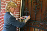 Peggy Lamn leaves a flyer on a door in the 3000 block of Cimarron St. Tuesday afternoon July 18,...