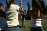 Young girls crowd in front of Ernestine Romero, 19, of Pojoaque, N.M., as she performs in the park...