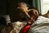 Tami Bishop, 36, of Denver sits with her two dogs Zander and Hidye in her house in south west...