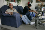Samuel Hernandez, CQ, 48,left, and his son Jesus Hernandez sit in the frontroom of their families...
