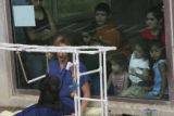 Umande learns to swing sitting safely on the lap of Tracey Gazibara, Caregiver Volunteer and Zoo...