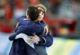 American speed skater Chad Hedrick (back to camera) gets a hug from one of his coaches after...