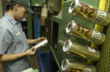 Jerry Brooks checks cans at the printer where labels are applied. This location produces 12 oz and...